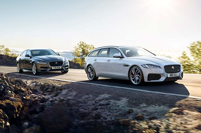 Jaguar XF Saloon and Sportbrake driving down a road.