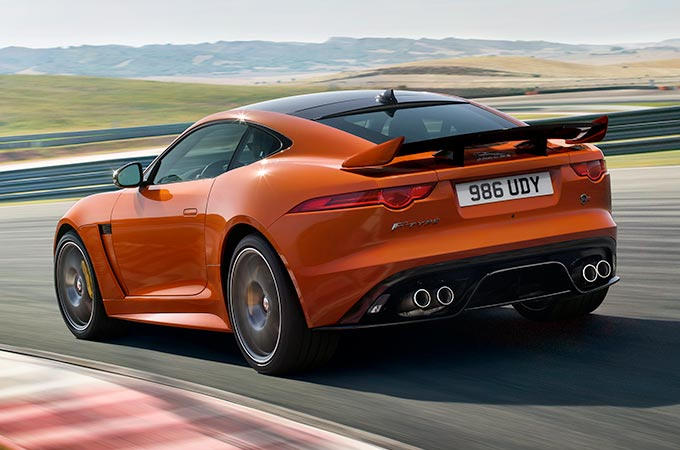 Jaguar F-TYPE in orange from behind going round a bend on a race track in sandy terrain.