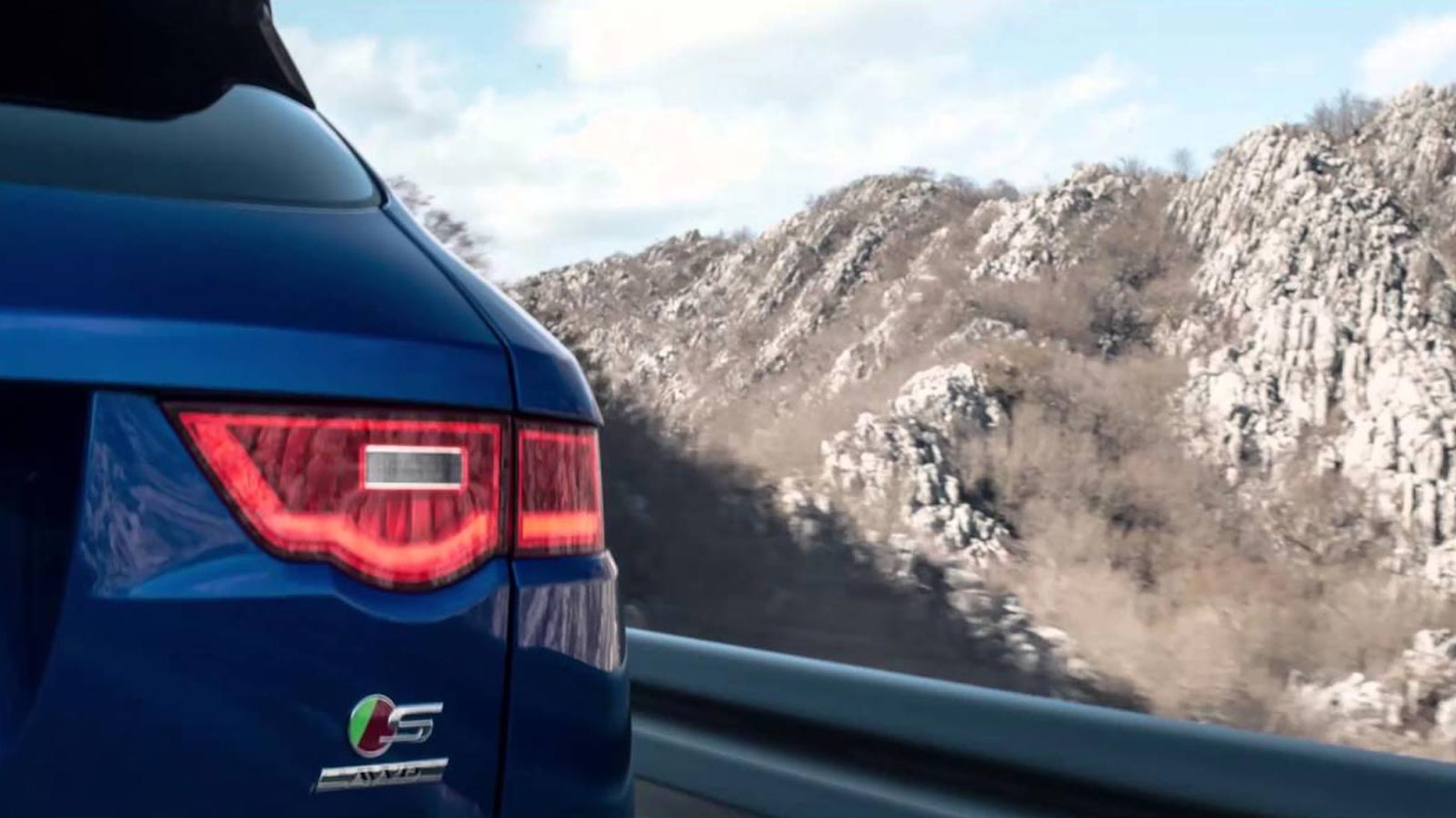 F-pace driving on a road by a mountain.