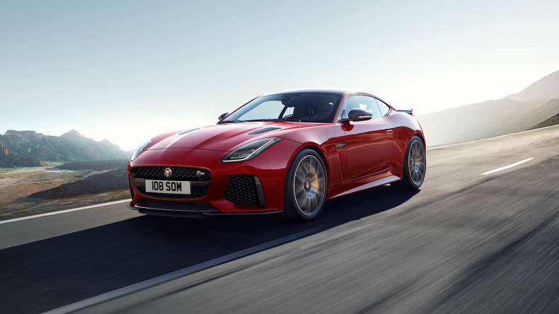 Red Jaguar F-type driving on road.