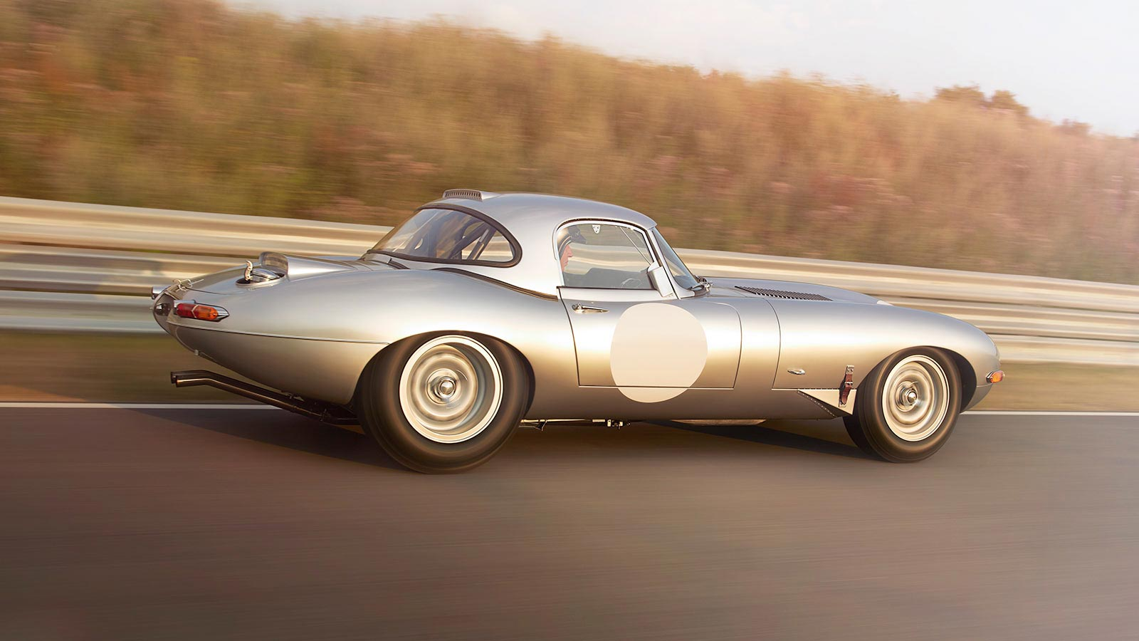 Jaguar Lightweight E-TYPE from the side on a race track.