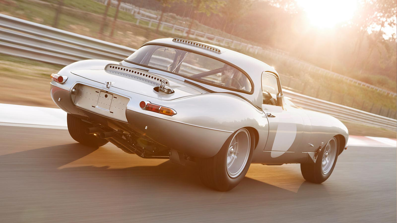 Jaguar Lightweight E-TYPE from behind driving on a race track.