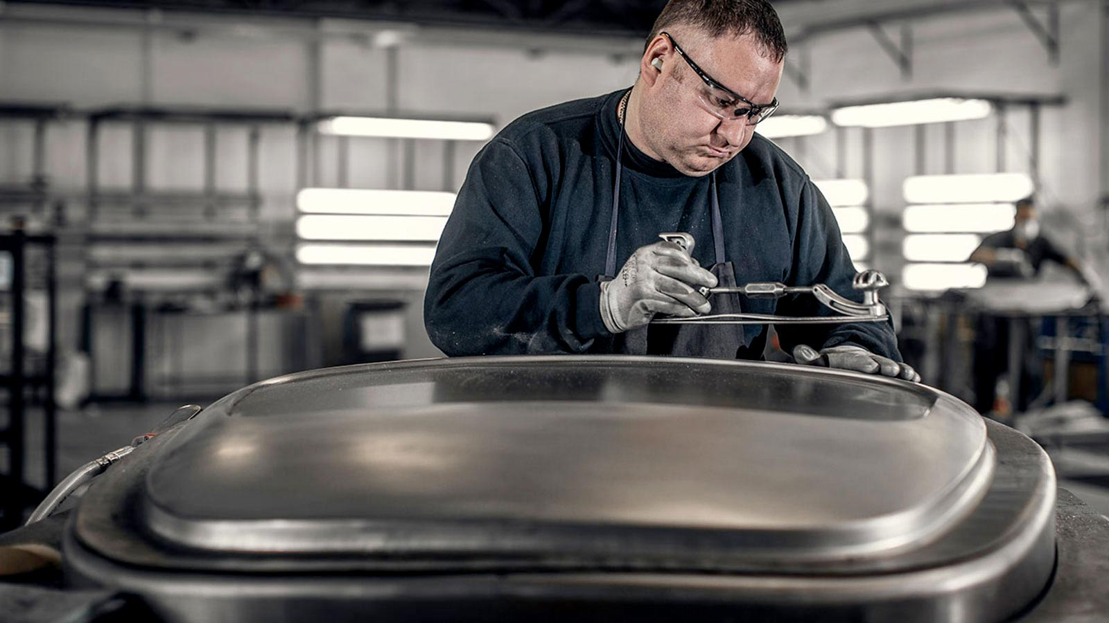 Mechanic working on a metal body-part for a vehicle.