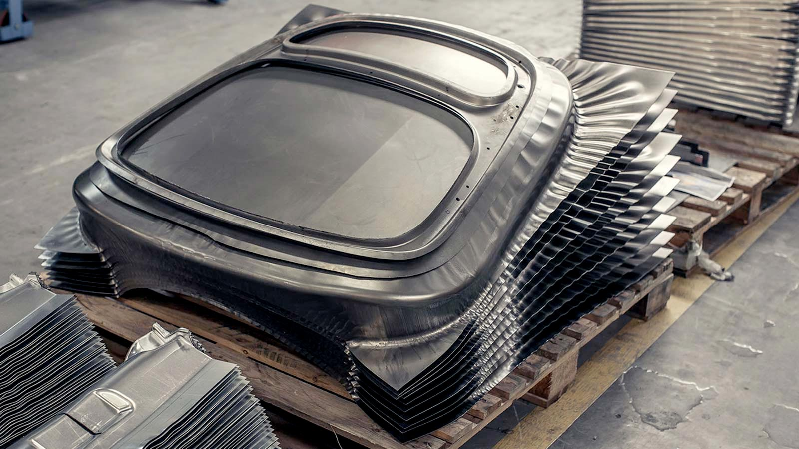 A pile of metal sheets shaped into a component of a car.