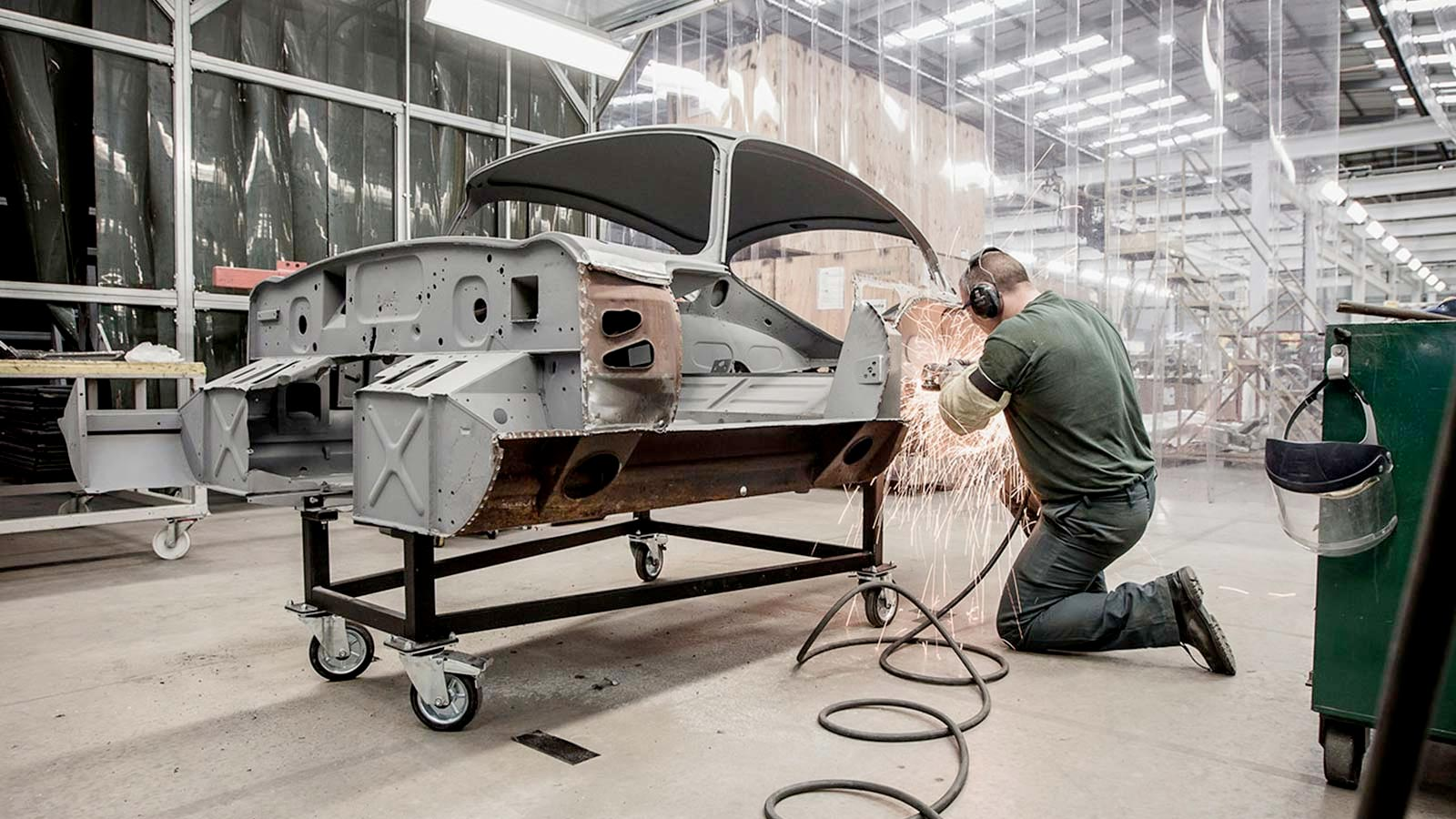 Mechanic working on the front of a chassis of an E-TYPE.