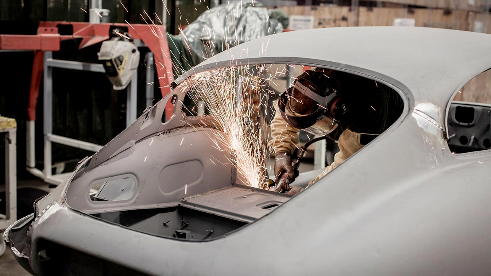 A mechanic working on the back of a chassis of an Jaguar E-TYPE.