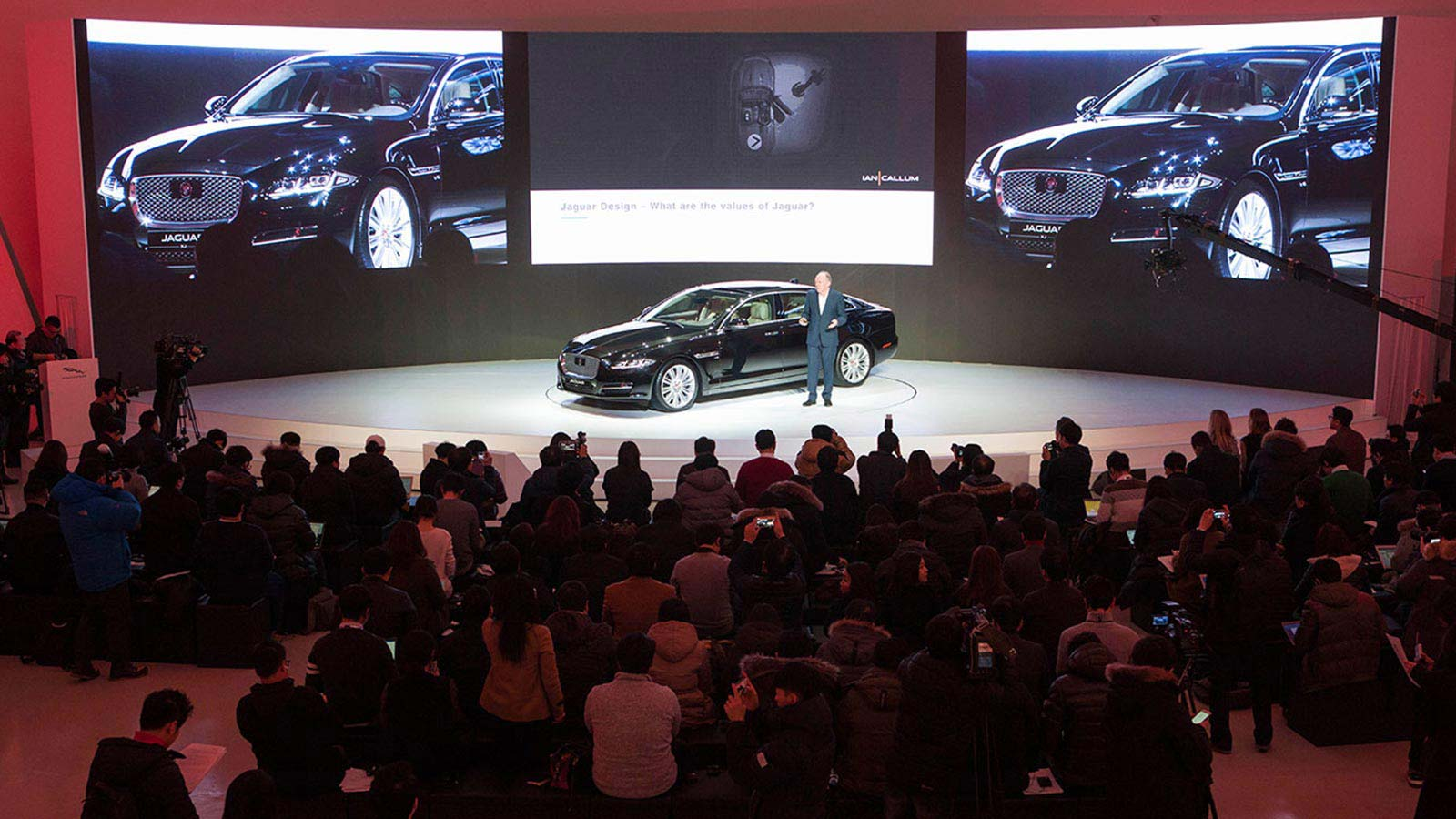 Director of Design, Ian Callum, giving a talk on stage next to a Jaguar XJ in black.