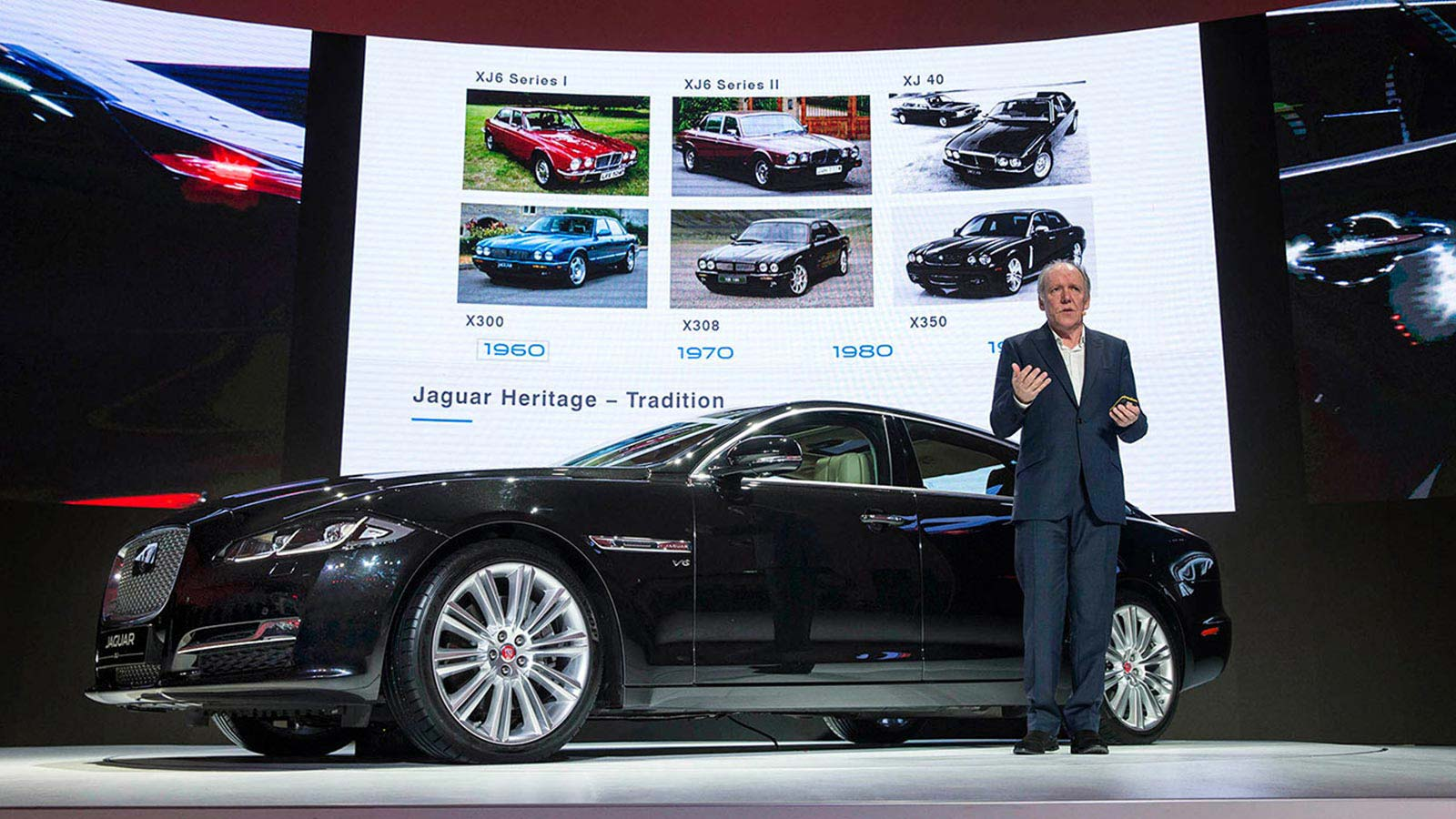 Director of Design, Ian Callum, talking about Jaguar Heritage whilst being stood next to a Jaguar XJ in black.