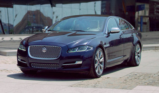 Jaguar XJ in navy exiting a building onto a street.