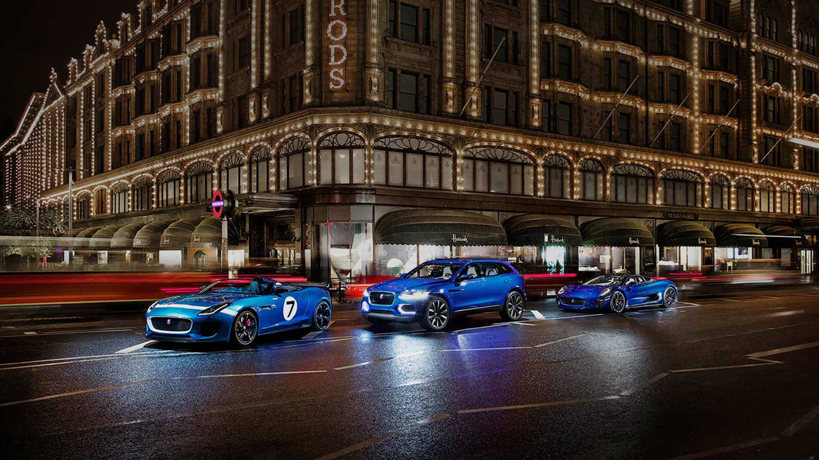 A lineup of a Jaguar Project 7, F-PACE and C-X75 Concept Car, all in blue outside Harrods in London at night.