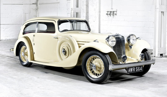 A white 1935 SS Jaguar 2.5l Saloon parked in a garage.