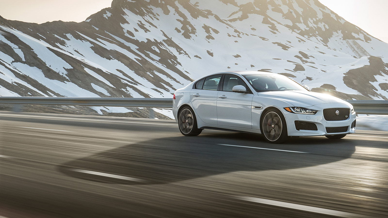 White Jaguar XE in Front of a Snowy Mountain.