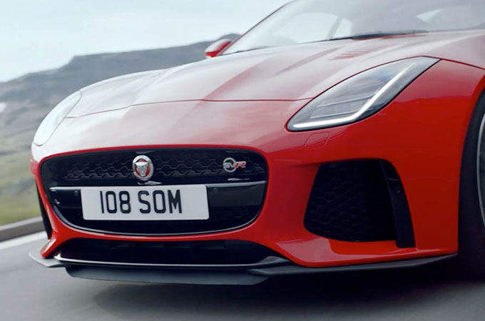 A closeup of the front of a Red Jaguar F-type driving on a road.