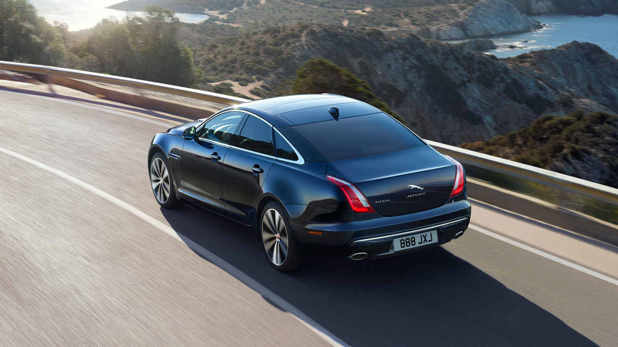 Jaguar XJ Driving On Road Near Mountains.