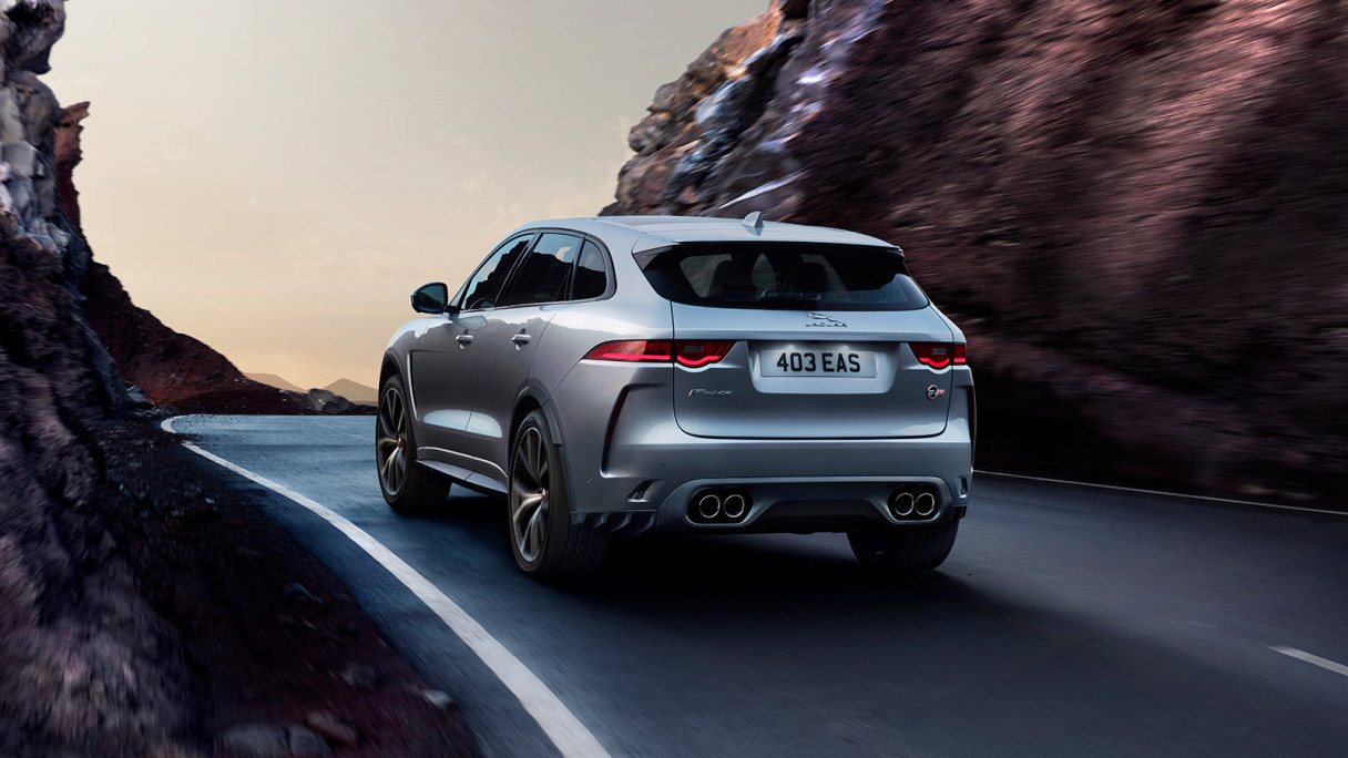 Jaguar F-PACE SVR in Indus Silver driving between volcanic rock.