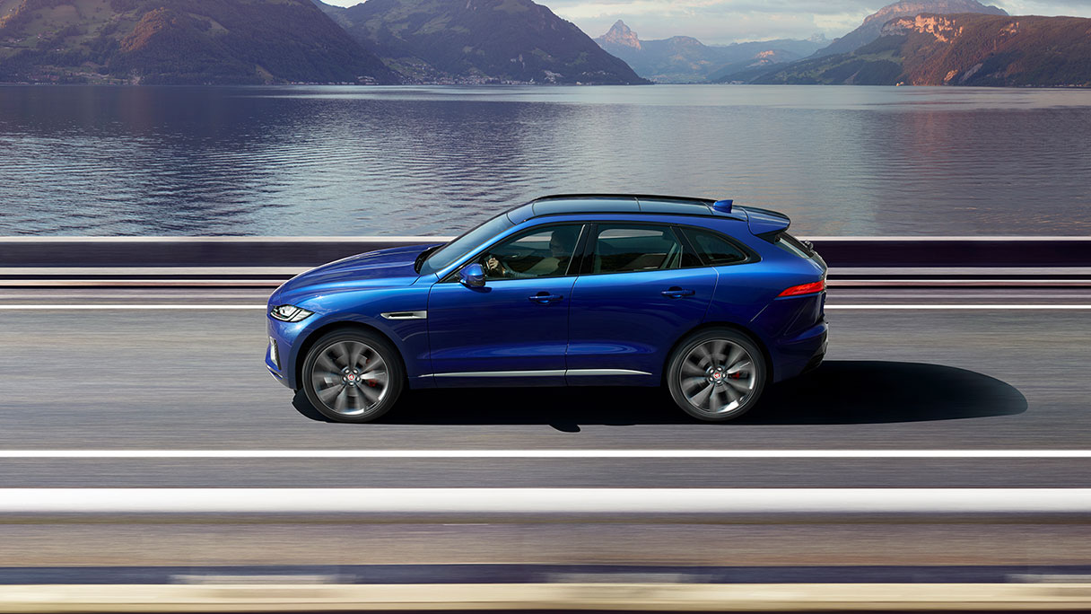Jaguar F-PACE driving along a road in front of a lake.