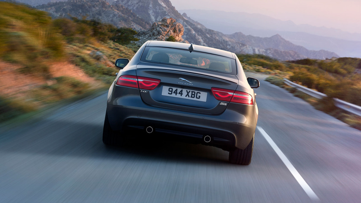 Rear view of Jaguar XE S, driving on-road, past mountains.