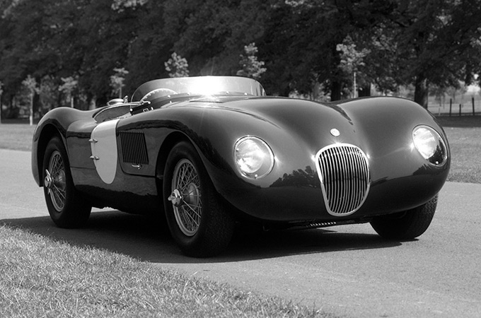 A 1951 Jaguar C-Type parked in front of some trees.