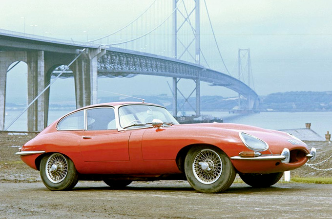 A red 1966 E-type Series 1 Coupe parked in front of a bridge.