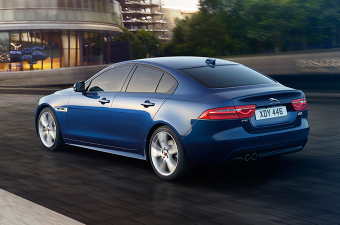A blue Jaguar XE driving in London.