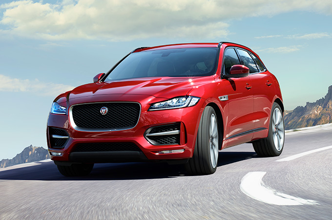 A red Jaguar F-PACE driving along a mountain road.
