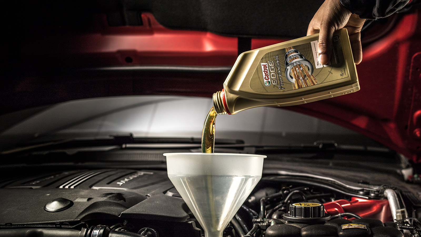 A bottle of Castrol EDGE professional oil being pored into a Jaguar engine.