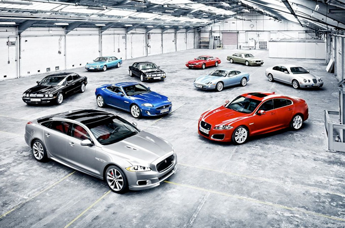 Various Jaguar models from the last 25 years of various colours parked in a warehouse.