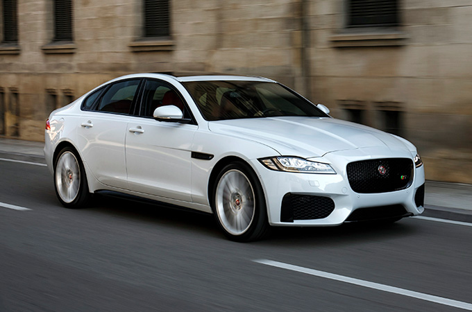 A white Jaguar XF S driving down a road.