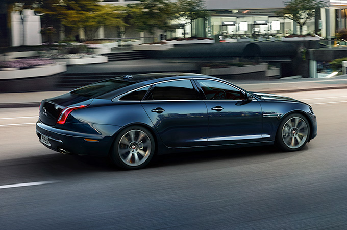 A black Jaguar XJ long wheel base driving down a road.