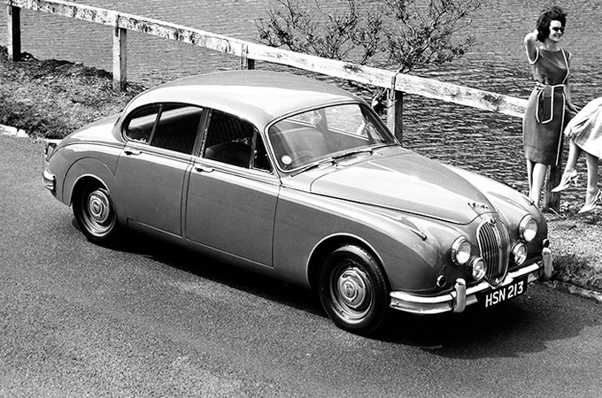 A 1962 Jaguar Mk2 parked next to a lake.