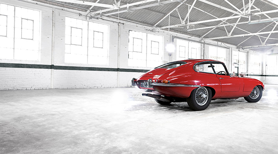 Jaguar E-TYPE Coupe in red parked in a warehouse.