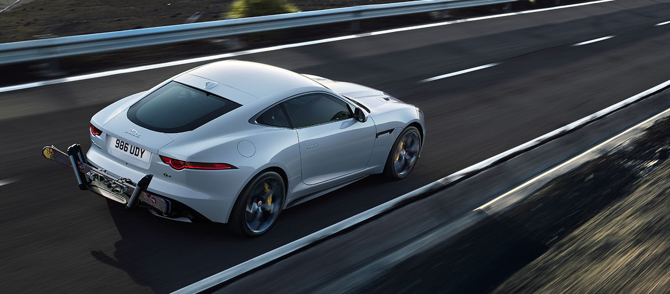 Jaguar F-TYPE Coupé Sports Car drives along an open road with a mounted ski carrier attached to the rear