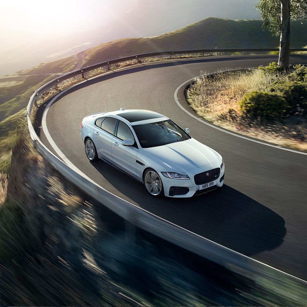 White Jaguar XF driven on road.