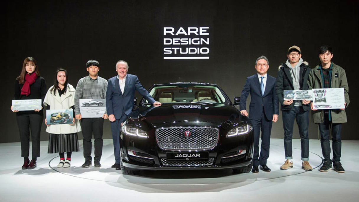 Director of Design, Ian Callum, stands by a Jaguar XJ alongside some aspiring car designers.