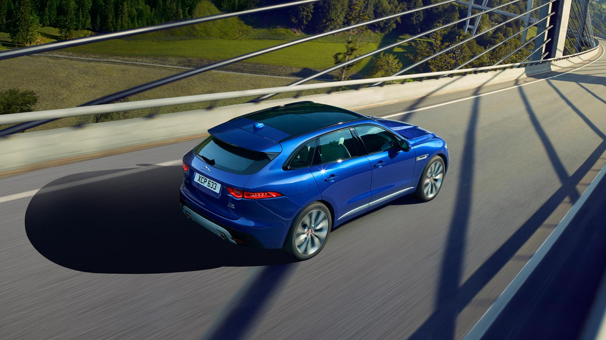 Blue Jaguar F-Pace Driving on road.