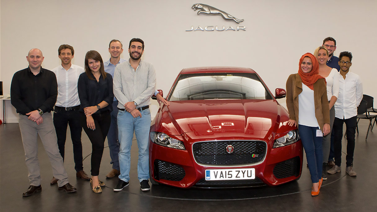 Two design students standing with red Jaguar.