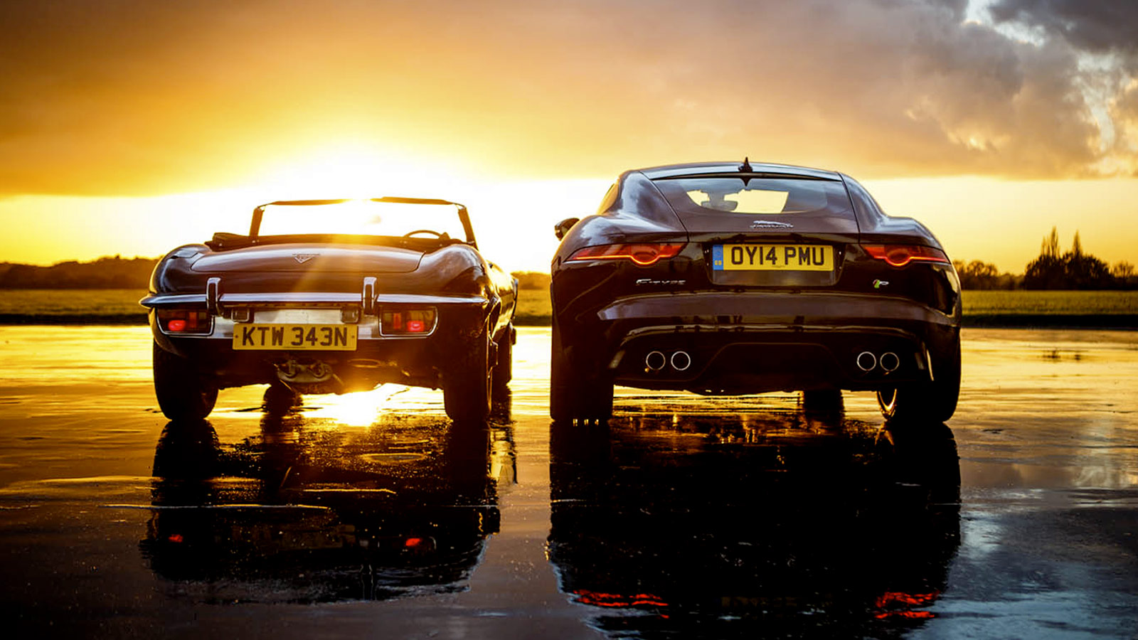 two jaguar's parked with the sunset behind.