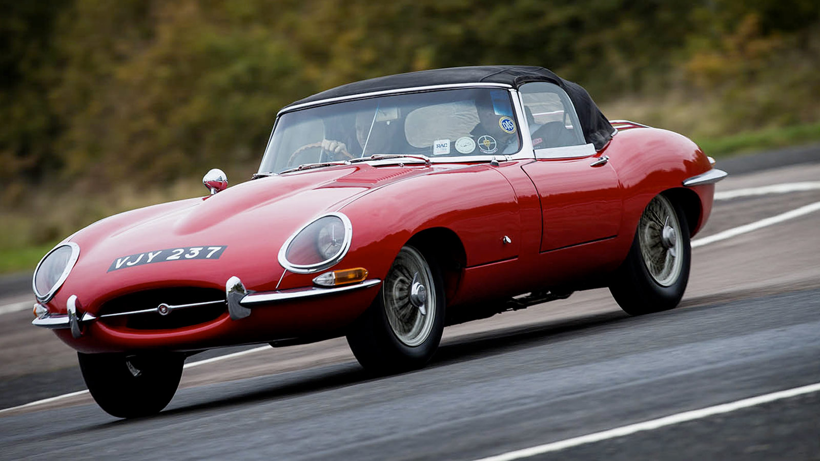 red classic Jaguar driving on road.