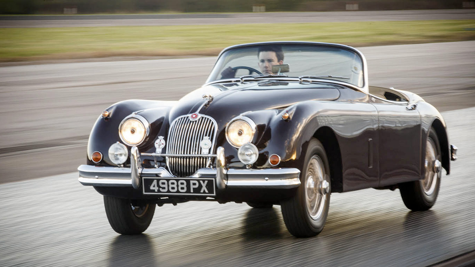 driving heritage jaguar on road.