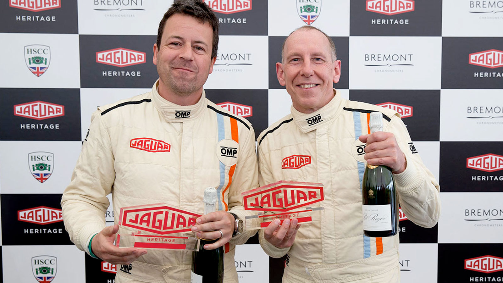 shot of two winners holding Jaguar trophies.
