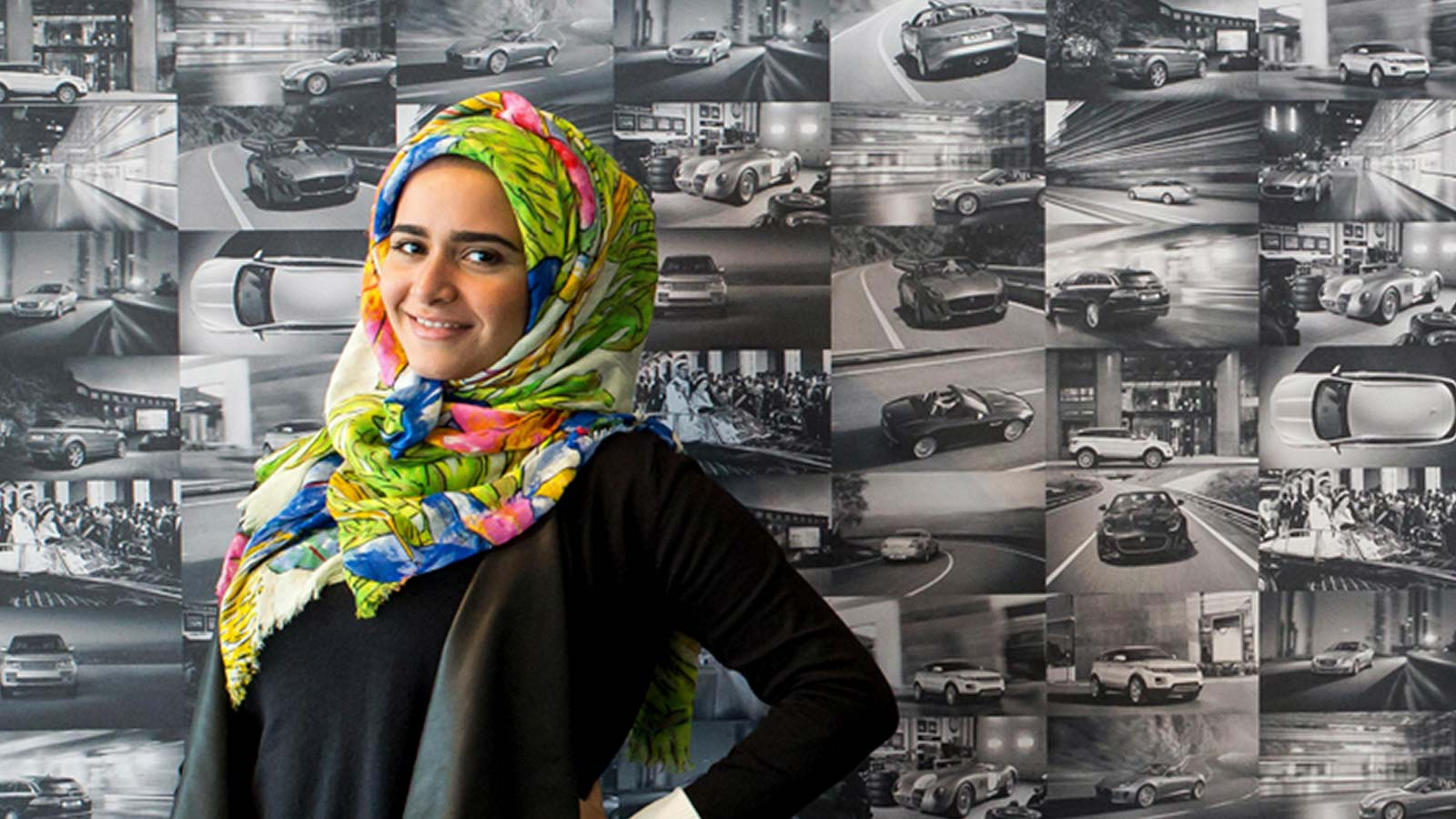 Design student stood in front of a wall made up of various photos of Jaguar Land Rover nameplates.