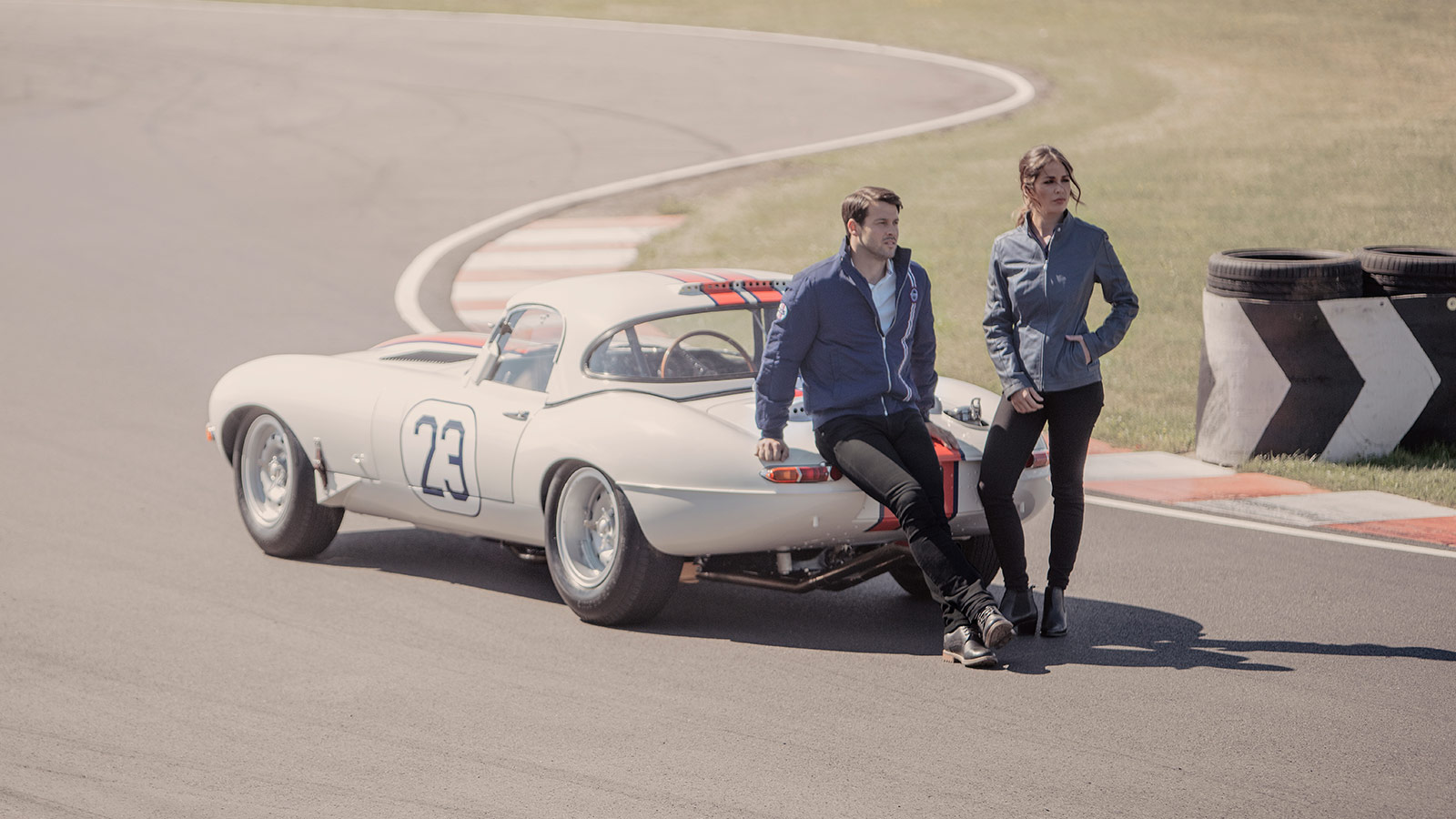 Man and Woman wearing Jaguar branded coats sitting on an E-type.