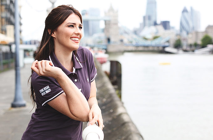Woman wearing a Jaguar branded polo shirt.