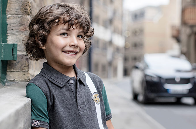 Small boy wearing a Jaguar branded polo shirt.