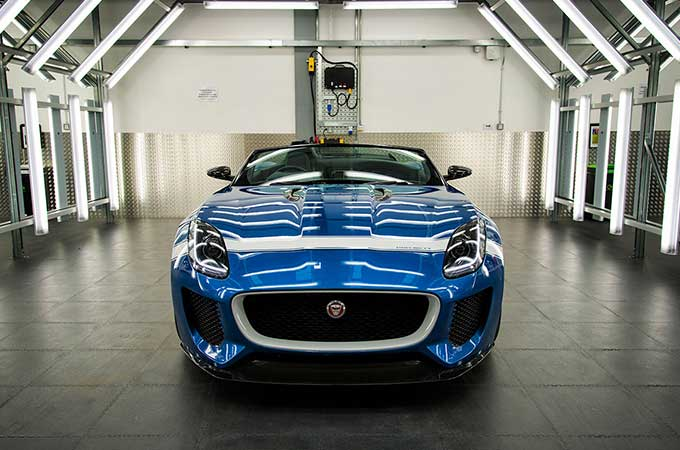 blue jaguar parked in a warehouse.