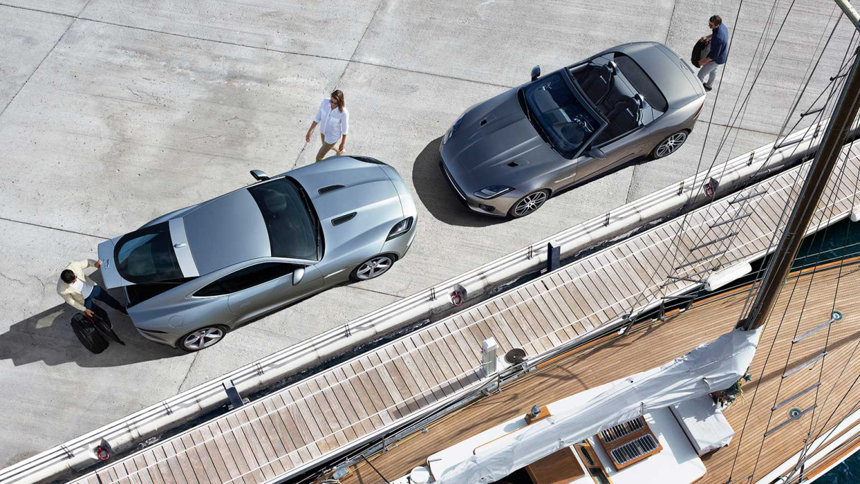 Jaguar F-TYPE Coupé and Convertible parked next to a boat.