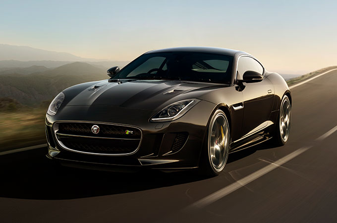 Black Jaguar F-TYPE Driving Down A Road.