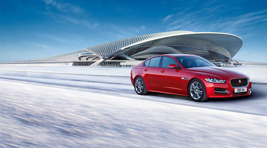 Jaguar XE in red driving on a snowy road in front of a large modern building.