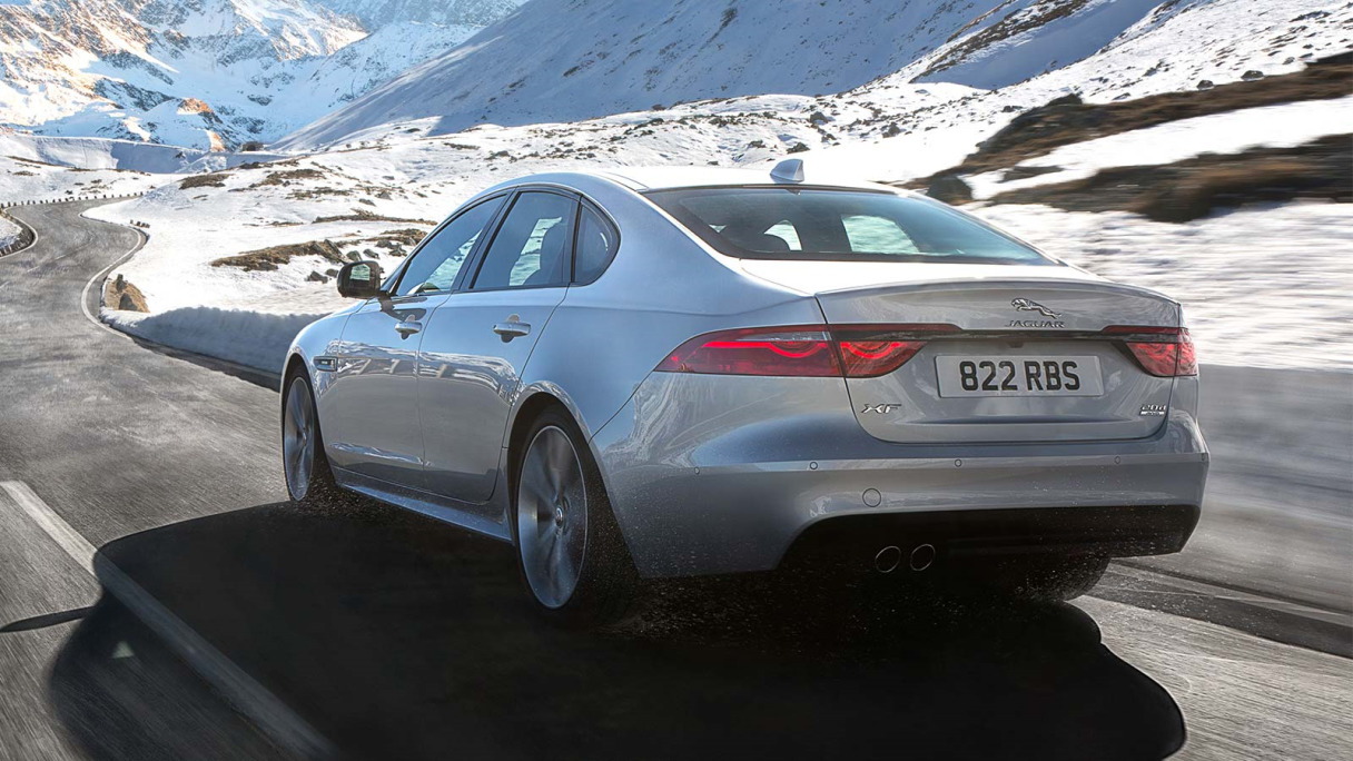 Jaguar XF in silver from behind driving on a road in a snowy landscape.