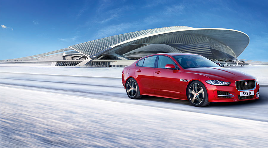 Jaguar XE in red driving on a road surrounded by snow and a large modern buildling.